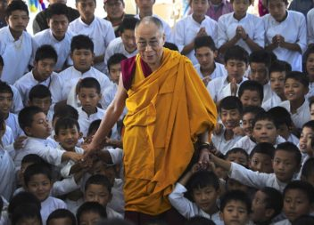 Exiled Tibetan spiritual leader the Dalai Lama poses for a picture with the students of a Tibetan school after inaugurating its auditorium at Gurupura in the southern Indian state of Karnataka on 14 July 2013.